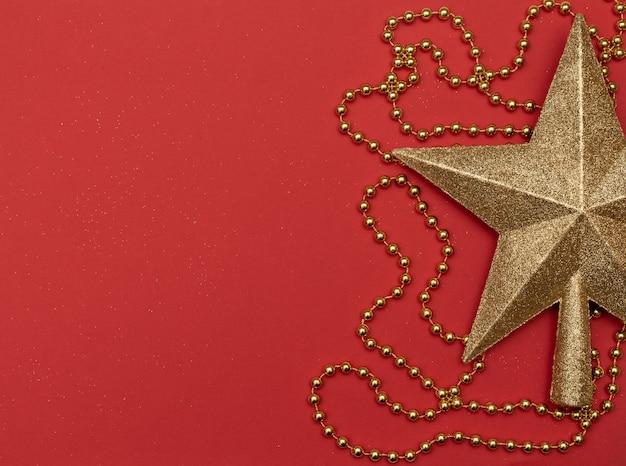Weihnachtsroter hintergrund mit goldenem stern - die spitze des weihnachtsbaums und der goldenen perlen.