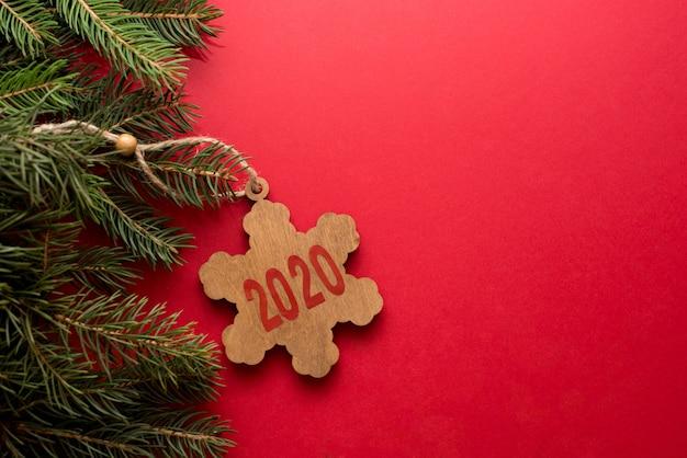 Weihnachtsroter hintergrund mit grünem baum und schneeflocke 2020 auf rotem hintergrund