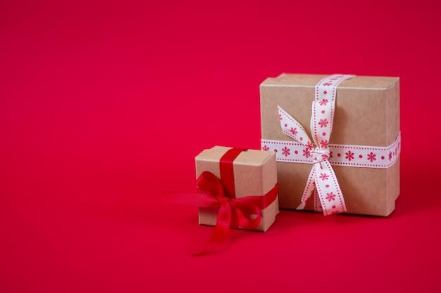 Weihnachtsroter hintergrund mit kleinen handgemachten geschenkboxen mit kopienraum