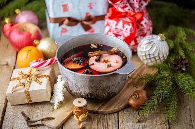 Weihnachtsrotwein glühwein mit gewürzen und früchten auf einem holztisch. winterkonzept. traditionelles heißes getränk zu weihnachten. glühwein mit zitrusfrüchten, äpfeln und gewürzen in einer pfanne.