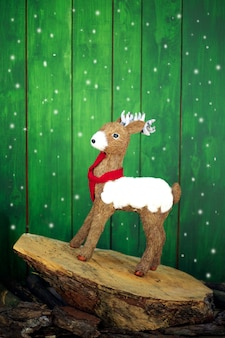 Weihnachtsrotwild auf einem stumpf und einem schnee.