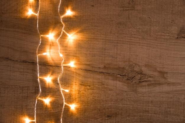 Weihnachtsrustikaler hintergrund - weinlese planked holz mit lichtern und raum des freien texts