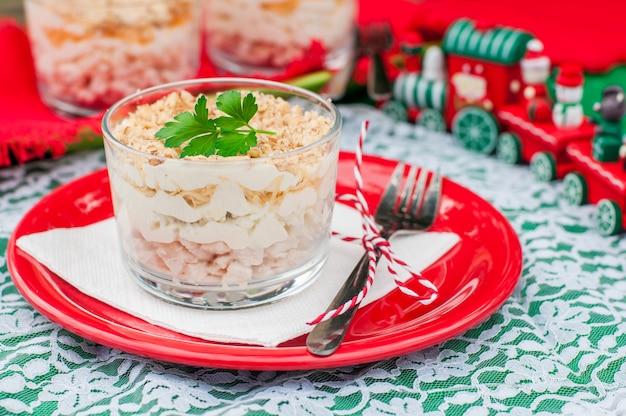 Weihnachtssalat mit hähnchen, apfel, käse und ei mit mayonnaise überzogen