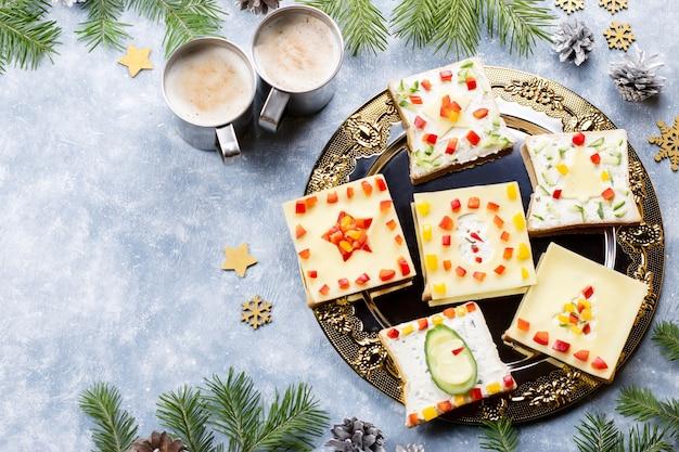 Weihnachtssandwiches mit käse und gemüse auf einem teller hautnah, ansicht von oben
