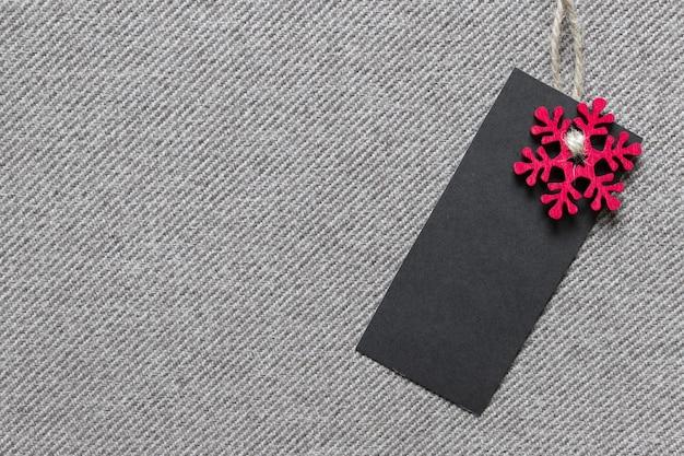 Weihnachtsschablonenmodell mit schwarzem leerem etikett und roter hölzerner schneeflocke auf strukturiertem stoff