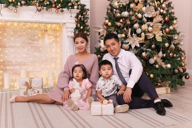 Weihnachtsschießkonzept, glückliche asiatische familie mit kindern, die geschenke durch den kamin und den baum geben