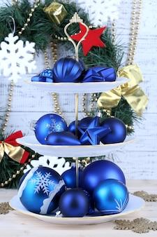 Weihnachtsschmuck auf dessertständer, auf farbigem holzhintergrund