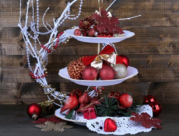 Weihnachtsschmuck auf dessertständer, auf holzuntergrund