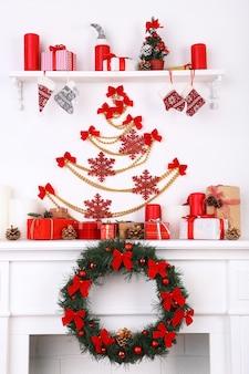Weihnachtsschmuck auf kaminsims auf weißem wandhintergrund