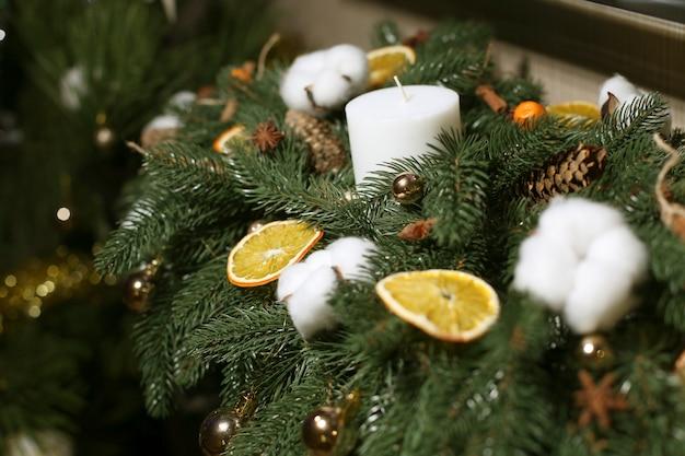 Weihnachtsschmuck aus künstlichem weihnachtsbaum, wattebällchen, zapfen, orangenscheiben und zimtstangen