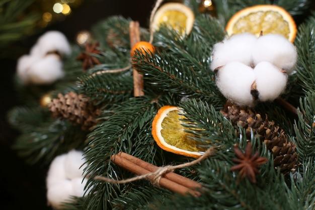 Weihnachtsschmuck aus künstlichem weihnachtsbaum, wattebäusche, zapfen, orangenscheiben.