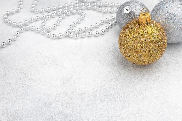 Weihnachtsschmuck der gold- und silberkugel auf unscharfem strukturiertem hintergrund mit raum für text
