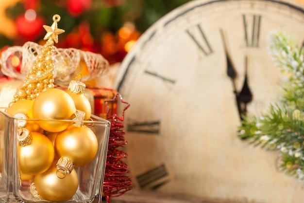 Weihnachtsschmuck gegen die alte uhr um mitternacht. neujahrskonzept