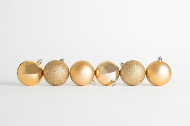 Weihnachtsschmuck, goldene kugeln auf weißem hintergrund