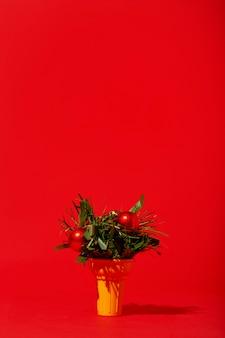 Weihnachtsschmuck in eistüte auf roter wand