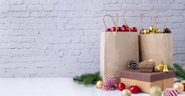 Weihnachtsschmuck in kraftpapier-einkaufstüten und geschenkbox.