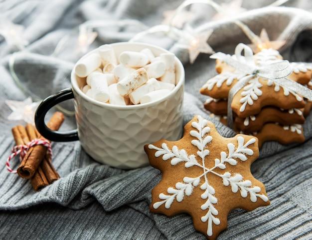 Weihnachtsschmuck, kakao und lebkuchen. weißer hölzerner hintergrund.