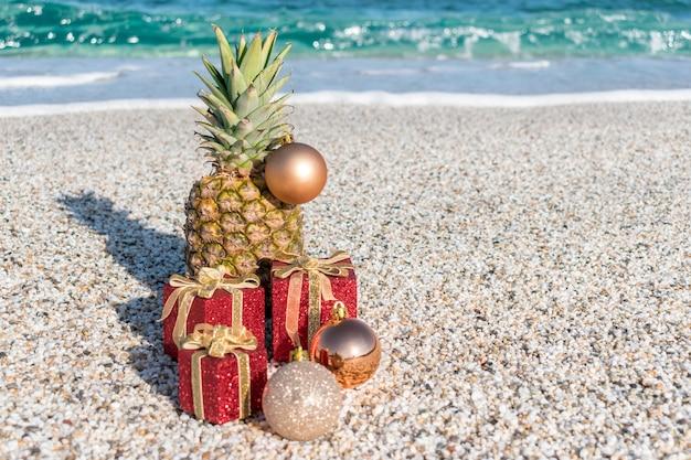 Weihnachtsschmuck, kugeln und ananas an einem sandstrand
