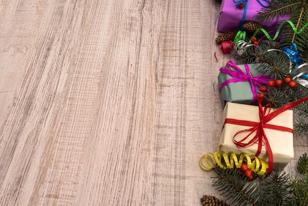 Weihnachtsschmuck mit tannenzweigen auf holztisch. geschenkboxen mit bändern. präsentiert konzept
