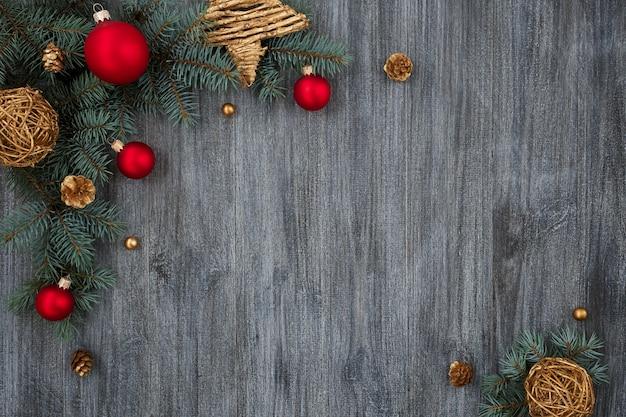 Weihnachtsschmuck, rote und goldene kugeln auf grauem holztisch