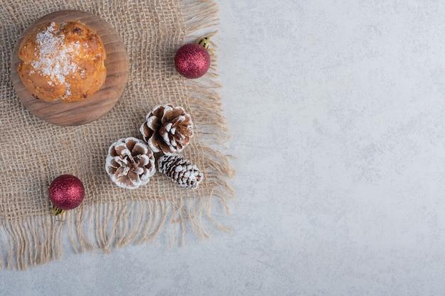 Weihnachtsschmuck und ein cupcake auf einem stück stoff auf marmoroberfläche