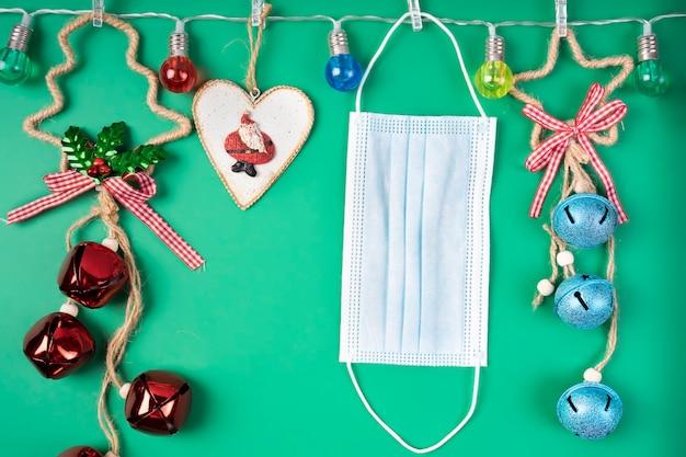 Weihnachtsschmuck und eine medizinische maske hängen von einer girlande aus bunten lichtern. quarantänekonzept zu weihnachten