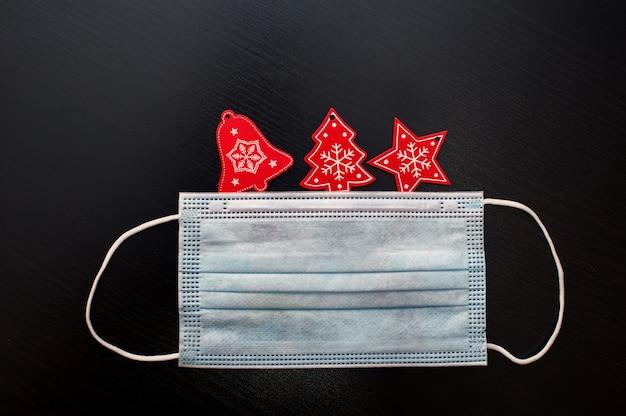 Weihnachtsschmuck und gesichtsmaske auf schwarzem hintergrund