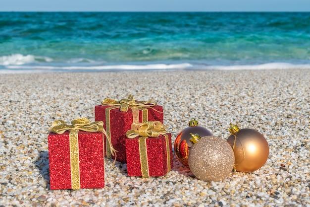 Weihnachtsschmuck und kugeln im sand am strand