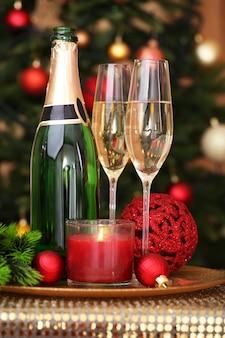 Weihnachtsschmuck und sektflasche und gläser auf heller oberfläche
