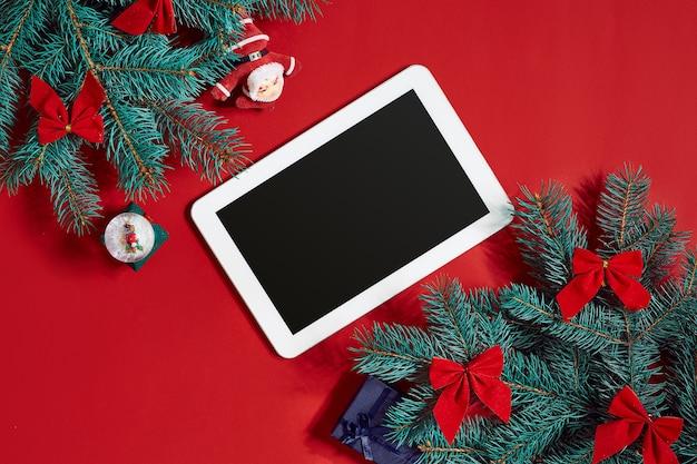 Weihnachtsschmuck und weiße tablette mit schwarzem bildschirm auf heißem rotem hintergrund. thema weihnachten und neujahr. platz für ihren text, wünsche, logo. attrappe, lehrmodell, simulation. ansicht von oben. platz kopieren. stillleben. flach liegen.