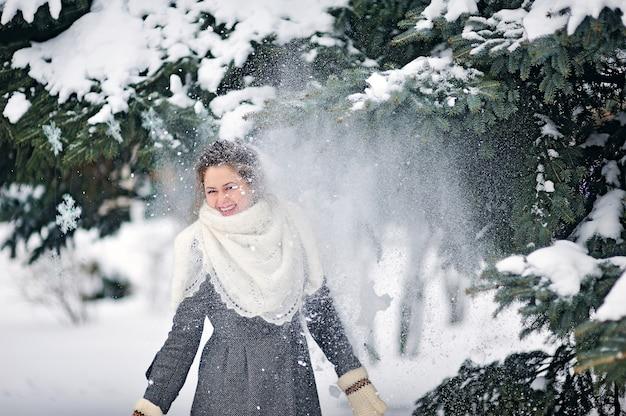 Weihnachtsschnee fliegt auf ein mädchen im park im winter mit schneebedeckten bäumen