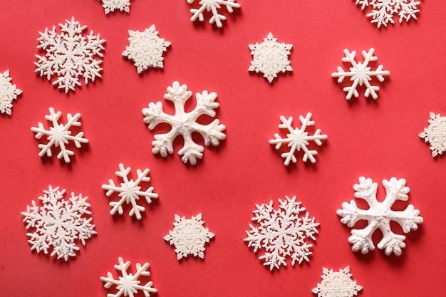 Weihnachtsschneeflocken unterschiedlicher form auf rot. weihnachtsfeiertag.