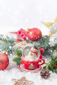 Weihnachtsschneekugel mit tannenzweigen und festlichen dekorationen auf schneetisch. weihnachts- oder neujahrskonzept
