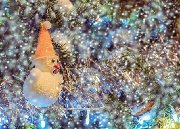 Weihnachtsschneemann auf weihnachtsbaum mit schneefällen