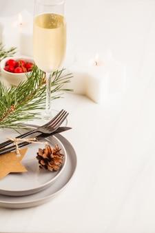 Weihnachtsschönes gedeck mit champagner und kerzen. weihnachtspostkarte.