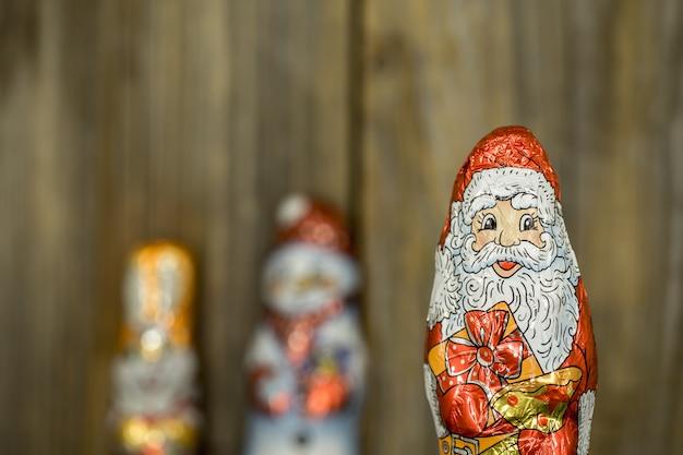 Weihnachtsschokoladenfiguren in einer hülle auf holz