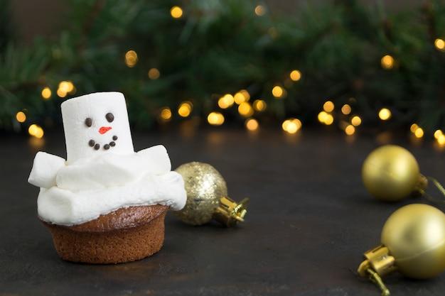 Weihnachtsschokoladenkleine kuchen mit schneemanndekor.