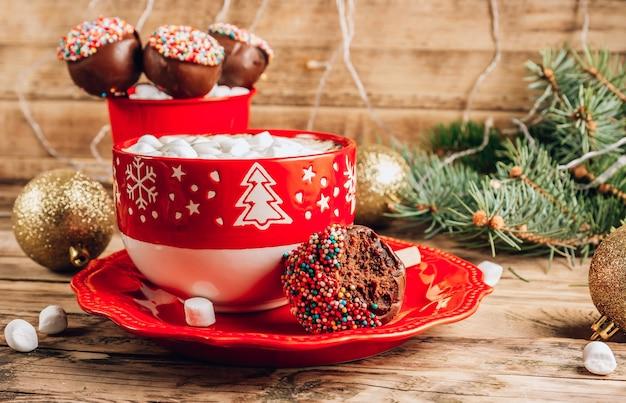 Weihnachtsschokoladenkuchen knallt im roten korb mit tasse kaffee mit marshmallows