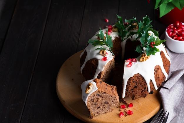 Weihnachtsschokoladenkuchen mit weißen zuckerglasur- und granatapfelkernen auf einer hölzernen dunkelheit mit roter laterne und poinsettia