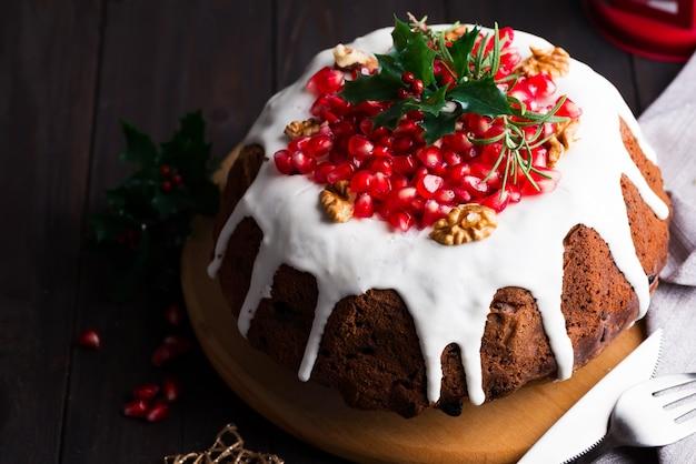 Weihnachtsschokoladenkuchen mit weißen zuckerglasur- und granatapfelkernen auf einer hölzernen dunkelheit mit roter laterne