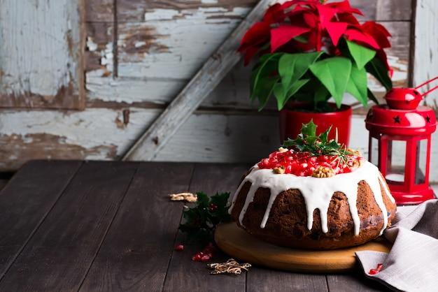 Weihnachtsschokoladenkuchen mit weißer zuckerglasur und granatapfelkernen eine hölzerne dunkelheit mit roter laterne und poinsettia