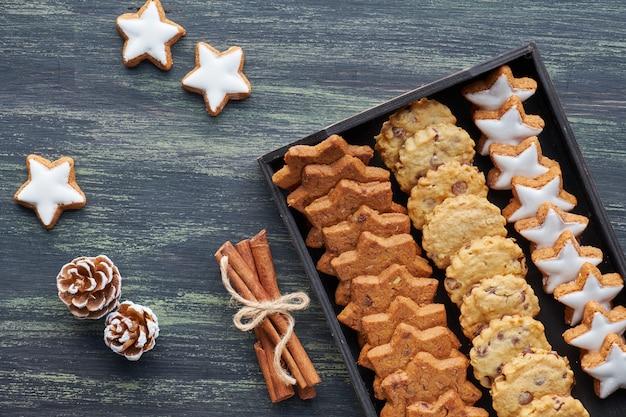 Weihnachtsschokoladensplitterplätzchen, flache lage mit gewürzen und winterdekorationen auf dunkelheit