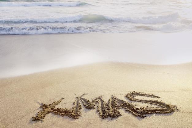 Weihnachtsschriften am tropischen strand, der zum meer in bali geschlossen ist. festliches warmes konzept.