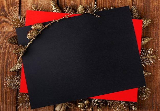 Weihnachtsschwarze karte mit festlicher goldener verzierung auf hölzernem hintergrund.
