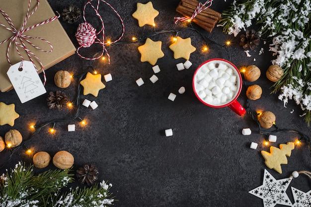 Weihnachtsschwarzer hintergrund mit kakao, girlande und verschiedenen verzierungen