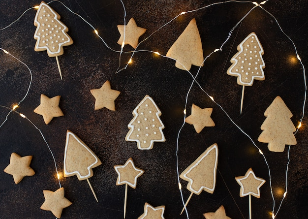 Weihnachtsselbst gemachtes lebkuchenplätzchen auf einer dunkelbraunen oberfläche