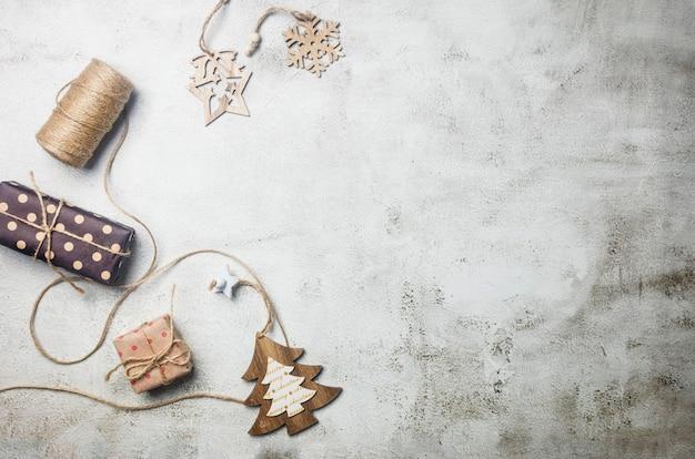 Weihnachtsset mit geschenken in bastelpapier, süßem holzspielzeug für den weihnachtsbaum, dekorationen auf hellgrauem hintergrund. silvester- oder winterabendkomposition. konzept der weihnachtszeit. grußkarte,