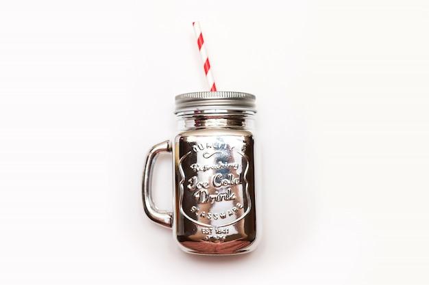 Weihnachtssilbernes weckglas mit dem stroh getrennt auf weißem hintergrund