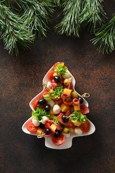 Weihnachtssnacks als häppchen in form eines weihnachtsbaumtellers für eine festliche weihnachtsfeier