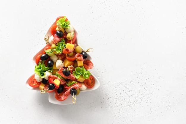 Weihnachtssnacks als häppchen in form eines weihnachtsbaumtellers für eine festliche weihnachtsfeier.